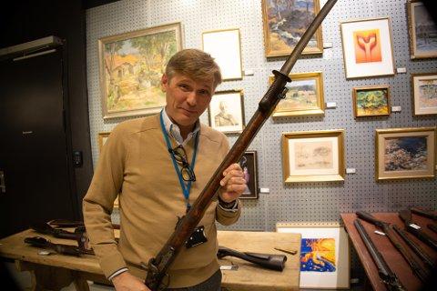 Samlergjenstander: Seniorekspert ved Blomqvist nettauksjon, Trond Schøning, viser fram et gammelt gevær som de regner med å selge for opptil 40.000 kroner. Bildene i bakgrunnen er også verdt mye penger.