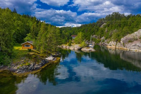 ENORMT: Tomta er på 500 mål med en idyllisk beliggenhet nær sjøen. Hovedhuset ses midt på bildet, mens hytta ses til venstre.