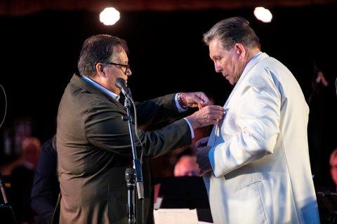 HEDRET: Statsforvalter Per Arne Olsen fester Kongens fortjenstmedalje på jakka til en rørt Øyvind Strand.