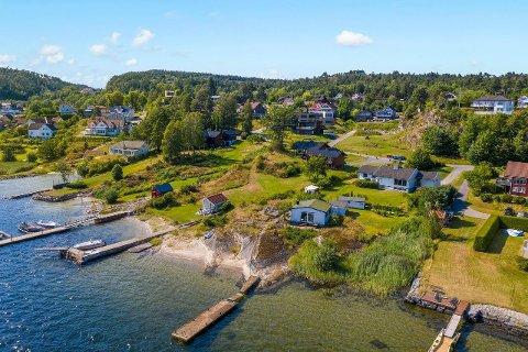 ATTRAKTIVT: Den mer enn tre mål store eiendommen består av en romslig enebolig, hytte, anneks og egen brygge og sandstrand.