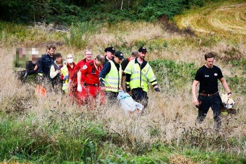 REDDET NED: Ambulansepersonell og brannmannskapet hadde vanskelige arbeidsforhold da de fraktet klatreren ned. Foto: Jarle Pedersen