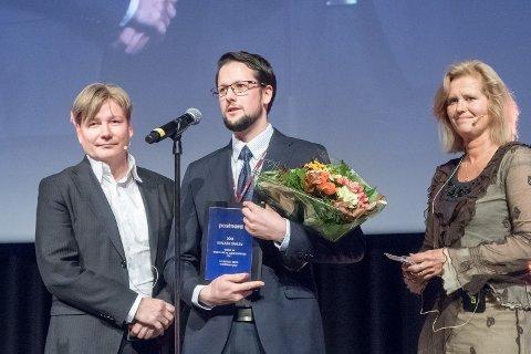 Odin Kvalvåg Dahlen (i midten) mottar prisen for beste masteroppgave på vegne av seg selv og Andreas Møll Kleiven.
