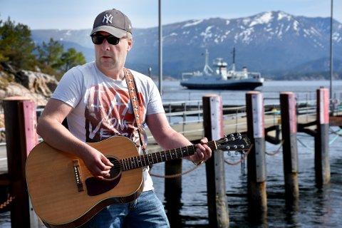 """Erling Holten jobber som matros på """"Bjørnsund"""" som kommer seilende i bakgrunnen. Men i helga holder han konsert på Veiholmen i forbindelse med sitt debutalbum."""