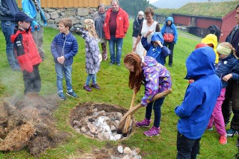 Isabella Smedsrud fra Kristiansund syntes det var spennende å lære mer om steinalderen på arrangementet på Tingvoll museum. Her plukker hun bort steiner fra kokegropen hvor en laks ble stekt.