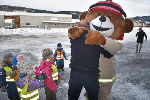 VELKOMMEN: Brannsjef Tor Arne Moen i Surnadal ønsker Bjørnis velkommen til brannstasjonen i Røtet med en god klem, mens spente barnehagebarn så vidt våger å tror det de ser ...
