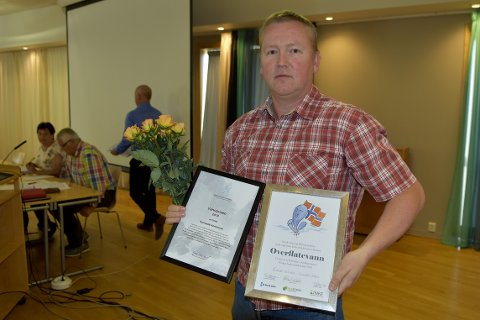 PRISET: Driftsleder Michal Heimlund i teknisk drift i Surnadal kommune, med blomster og priser for god kvalitet på drikkevannet til innbyggerne i kommunen.