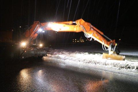 Hektisk gravearbeid for å lede vekk store vannmengder på fylkesvei 65.