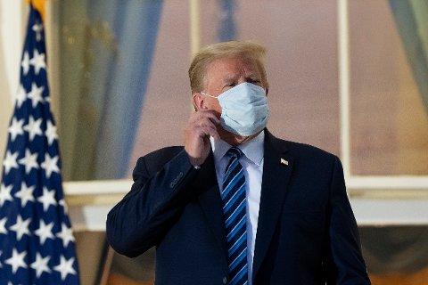 President Donald Trump tar av seg munnbindet før han går inn i Det hvite hus etter å ha blitt utskrevet fra Walter Reed-sykehuset.