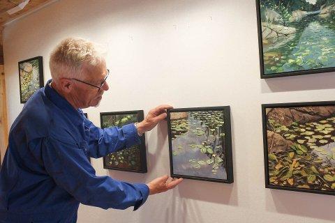 Per Kristian Solbakken henger opp malerier fra kunstutstillingen «Forty Friday Afternoons» av Magne Myhren. Lørdag 4.juli åpner galleriet.