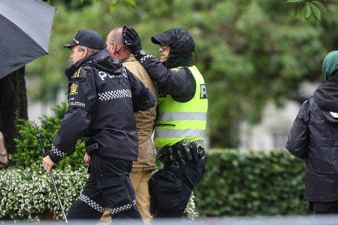 Sian-leder Lars Thorsen geleides bort fra podiet mens det ser ut som han blør fra hodet etter at det brøt ut uroligheter under Sians markering på Festplassen lørdag.