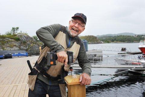 Humørsprederen Kjell Inge Jørgensen bruker fritida si i småbåthavna i Smenessundet. En meningsfylt hverdag er kjekt å ha for den pensjonerte tømreren som er travel med å bygge ut brygga og fronten foran nausta til småbåtlaget på Kårvåg.