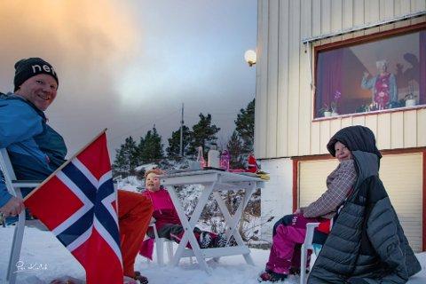 Målfrid Kvalvik (i vinduet) fyller 90 år. Barnebarnet Daniel Kvalvik tok med seg barna Mie (4) og Julie (7) og holdt selskap på betryggende koronaavstand utenfor stuevinduet til jubilanten.
