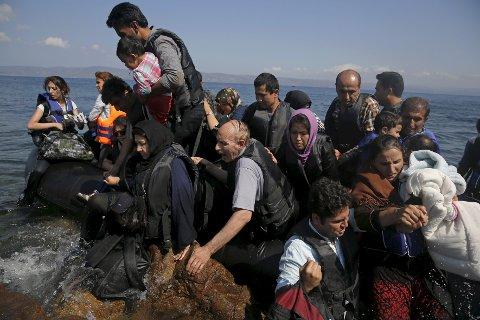 Disse afghanske flyktninger blir tatt hånd om av greske myndigheter på øya Lesbos. Grekerne fraktet fredag hundrevis av flyktninger fra de greske  øyene til fastlandet i et forsøk på å redusere det enorme flyktningepresset disse øyene opplever. Mange tusen flyktninger har flyktet fra borgerkrigen i Syria. Foto: Reuters/Alkis Konstantinidis