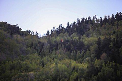 HENGER FAST: Den oransje paragliderskjermen vises midt på bildet. Øverst til venstre i bildet kan man skimte to personer. Disse står på kanten hopperne løper ut fra.