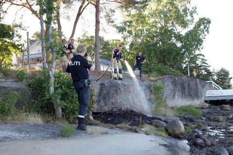 Brannmannskaper fra Vestfold interkommunale brannvesen slukker sankthansbålet som har blusset opp etter tre dager i vannkanten.