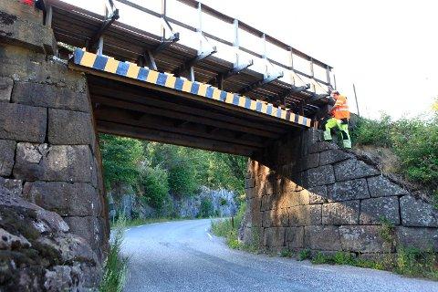 LØSNET: Stålbjelken ble slått løs i sammenstøtet med lastebilen. Her er banevakt for Vestfoldbanen, Kjetil Fjellaker, i gang med å inspisere skadene.