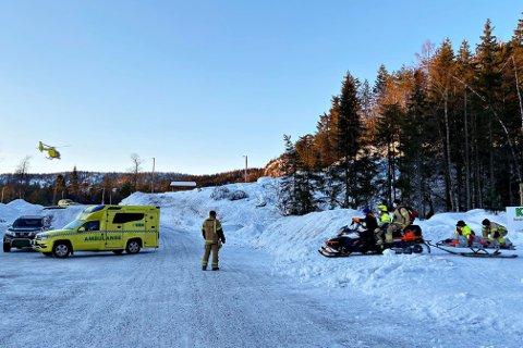 Her har nødetatene hentet ut den skadde skiløperen fra skogen. Luftambulansen kan skimtes i bakgrunnen.