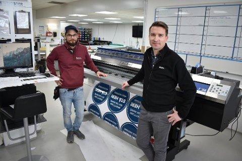 STORKONTRAKT: Daglig leder Kristian Hamar (t.h.) og de 16 andre ansatte hos Profil Grafisk i Kolbu har landet en fireårig kontrakt med Innlandet Fylkeskommune, som gir dem en sikkerhet i ei ustabil tid.