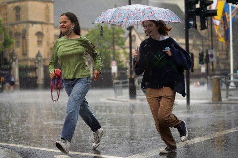 REGNTUNGT: To kvinner løper gjennom Parliament Square i London.