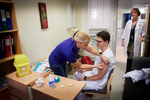 BIVIRKNINGER: AstraZeneca-vaksinen kan gi bivirkninger som feber og hodepine. Flere helsearbeidere har vært nødt til å holde seg hjemme fra døgn i et døgn eller to etter vaksinering, bekrefter Anne-Gro Fjellingsdal, smittevernkoordinator ved Helse Nord-Trøndelag. På bildet, som ble tatt i forbindelse med en reportasje om influensavaksine i 2018, følger hun med idet Rikard Meyer Sandling, som da var medisinstudent ved Sykehuset Levanger, får vaksine av bedriftssykepleier Lillian Solhaug.