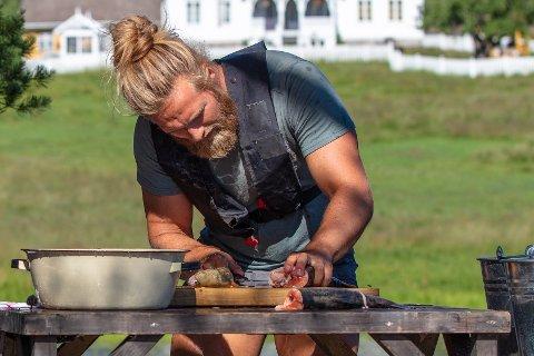 SLØYING AV FISK: Lasse Matberg var den raskeste av deltakerne til å hente opp og sløye fisk, selv om han måtte ro en ekstra tur ut med båten for å hente mer fisk.