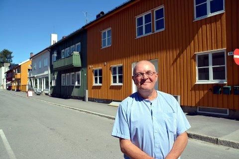 Gunnar Gravås skal flytte til Kirkegata, i bakgrunnen, og mener at det kan forsvinne opp til 1200 timer med sol i året med nybygget ved stasjonen.