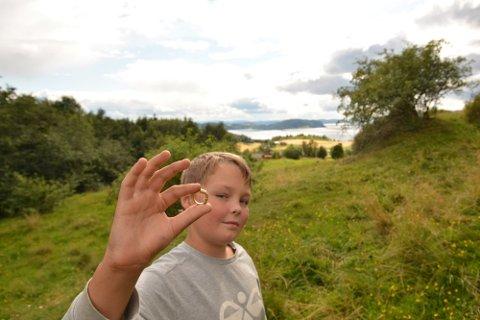 STOLT FINNER: Sander Skjærvik Vang (11) gjorde mandag det som kan vise seg å være et sjeldent funn. Gullringen han fant med metallsøkeren er trolig en betalingsring fra folkevandringstiden.