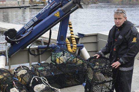 Teinefangst: Politioverbetjent Torvild Selås ombord på kommunens båt «Terna», med noen av de beslaglagte teinene. foto: olav loftesnes