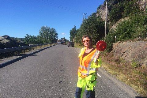 Mona Jacobsen stopper bilistene ved Åstø. Man risikerer å måtte vente i en og en halv time....