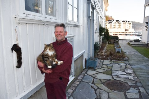 Trygve Johnsen med katten Tobias. PÅ veggen har Trygve hengt opp minktroféet.
