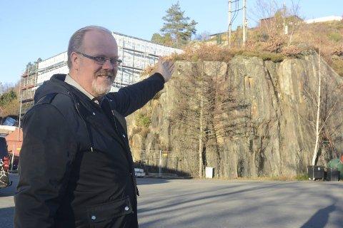 Planlegger: Svein Erik Damsgård peker opp mot fjellet der neste leilighetsbygg skal bygges. Det kommer litt venstre for høyspentmasta på bildet. Denne masta skal fjernes, etter at kraftlinjene i området er lagt i bakken.Foto: Øystein K. Darbo