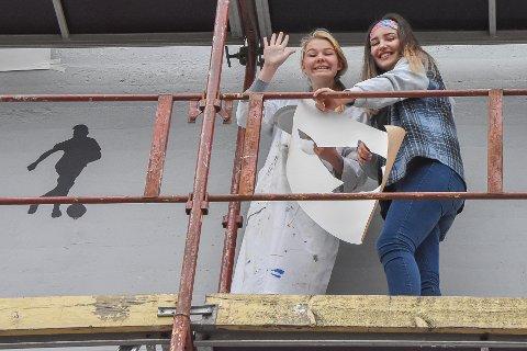 Charlotte og Misha forbereder seg til å feste Charlottes fiskemotiv til veggen.