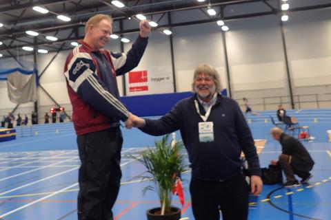 Finn Pedersen (th) blir gratulert av Kalle Glomsaker, som er styremedlems i Norge friidrettsforbund.