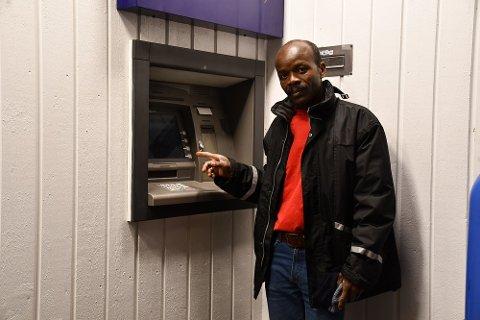 Allam Abdelshafie ved Sparebanken Sørs minibank i gågata i Tvedestrand, der en kunde glemte eller mistet pengene.