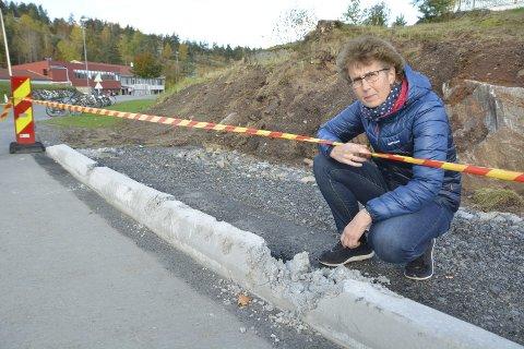 Overgitt: Liv Strand ved et av stedene hvor betongkanten til det nye fortauet er blitt ødelagt i løpet av helgen. Foto: Frode Gustavsen