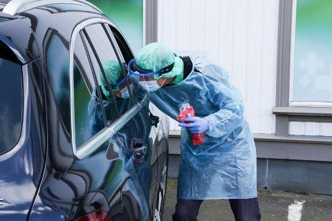 Lege ved Tvedestrand legesenter Georg Smedsaas gjennomfører testene gjennom bilvinduet.
