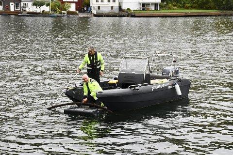 Tvedestrand havn: Roar Solheim og Kåre Lillebø i Tvedestrand kommune rykket ut i båt for å få pumpeledningen ned på dypet. Foto: Marianne Drivdal