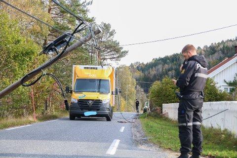 Politiet måtte sperre veien en times tid mandag formiddag, da en kranbil dro med seg både strømledninger og stolpe ved Laget kirke. (Den gule varebilen på bildet, var ikke den skyldige, men kommer etter kranbilen og ble stående fast).