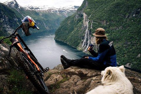 Nyter utsikten: Sammen med to av sine bestevenner, sykkelen og Samojed-hunden Ulla, ser «Makken» utover Geirangerfjorden. FOTO: EMIL SOLLIE.