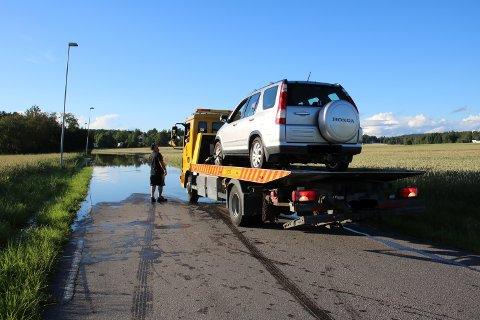 To biler ble ødelagte etter å ha kjørt i flomvannet i Hølen tirsdag kveld. Her blir den ene fraktet bort av bilberger.