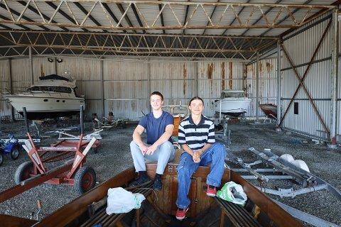 """NESTE: F.v. Oscar Malcolm Erlandsen (17) og Petur Asgeir Petursson (17) har gjort det til noe sosialt å jobbe mot målet om å få snekka """"Hygga"""" sjøsatt i løpet av sommeren."""