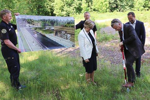 Horten-ordfører Are Karlsen tar det første spadestikket i Redningsselskapets gigantprosjekt på Langgrunn i Horten. Om et drøyt år vil det se ut slik som på bildet i bakgrunnen.