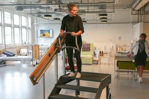 Ingrid Lonar, teknisk sjef og medgründer i AssiStep, viser hvordan oppfinnelsen skal gjøre det enklere å gå i trapper.
