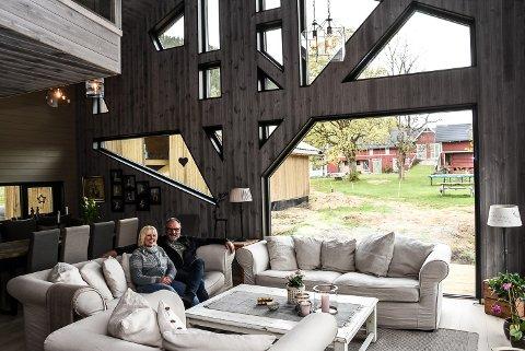 FRA STUA: Ragnar og Else Grete Engebretsen i den nye stua si. Hele veggen er et lite kunstverk...