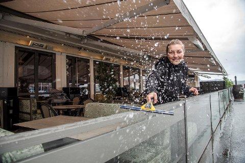 Rebecca Amlie (20), servitør på restauranten Olivia på Zachariasbryggen, må bruke nal for å få vekk alt regnet før åpning av uteserveringen.