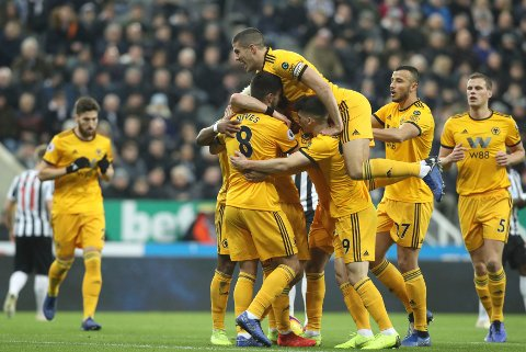 Wolverhampton Wanderers' Diogo Jota, obscured, is mobbed by team-mates celebrating scoring his side's first goal of the game against Newcastle United during their English Premier League soccer match at St James' Park in Newcastle, England, Sunday Dec. 9, 2018. (Owen Humphreys/PA via AP)
