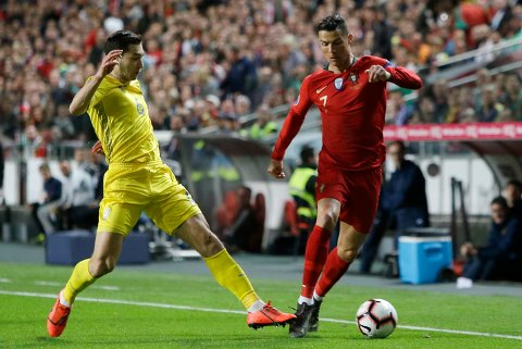 Portugal's Cristiano Ronaldo, right, dribbles past Ukraine's Taras Stepanenko during the Euro 2020 group B qualifying soccer match between Portugal and Ukraine at the Luz stadium in Lisbon, Friday, March 22, 2019. (AP Photo/Armando Franca)