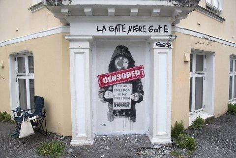 Gatekunstneren AFK hengte opp et bilde på den mye omtalte veggen i natt. En skikkelse med stor jakke og hette, og et hode formet som en jordklode, holder en plakat med teksten «Press freedom is my freedom». Under står «We are millions» og «free Assange».