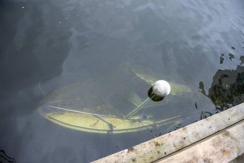 Ved en kai på Damsgård ligger en båt godt under havoverflaten. Det er grunneiers plikt å fjerne den.