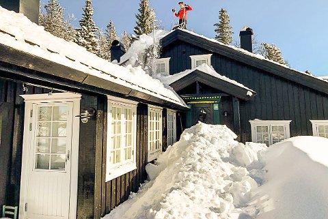TUNG SNØ: Geir Erland Kolbjørnsrud fjernet torsdag store mengder med snø fra dette hyttetaket på Tempelseter.